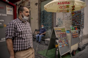 """A waiter (left) and a peddler (right) are seen in the """"Quartieri Spagnoli"""" in Naples, Italy on June 16, 2020. Popular neighborhoods are those that more than others are suffering from the economic crisis generated by the coronavirus. The rate of poverty and unemployment that was higher than the national average in Southern Italy even before the pandemic, increased following the lockdown imposed by the government to counter the spread of the coronavirus, which blocked the country's economy for more than two months."""