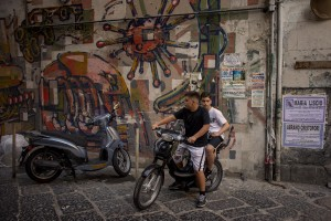 """Two kids are seen on a scooter in a street of the """"Rione Sanità"""" in Naples, Italy on June 17, 2020. Popular neighborhoods are those that more than others are suffering from the economic crisis generated by the coronavirus. The rate of poverty and unemployment that was higher than the national average in Southern Italy even before the pandemic, increased following the lockdown imposed by the government to counter the spread of the coronavirus, which blocked the country's economy for more than two months."""
