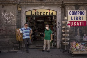 Two men are seen outside a library in Dante square in Naples, Southern Italy on June 15, 2020.