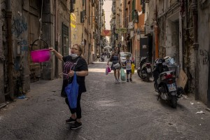 """A woman takes items from a basket in the """"Quartieri Spagnoli"""" in Naples, Italy on June 16, 2020. Popular neighborhoods are those that more than others are suffering from the economic crisis generated by the coronavirus. The rate of poverty and unemployment that was higher than the national average in Southern Italy even before the pandemic, increased following the lockdown imposed by the government to counter the spread of the coronavirus, which blocked the country's economy for more than two months."""