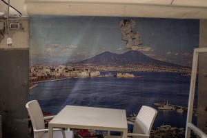"""A poster depicting Mount Vesuvius is seen outside a pizzeria in the """"Quartieri Spagnoli"""" in Naples, Italy on June 16, 2020. Popular neighborhoods are those that more than others are suffering from the economic crisis generated by the coronavirus. The rate of poverty and unemployment that was higher than the national average in Southern Italy even before the pandemic, increased following the lockdown imposed by the government to counter the spread of the coronavirus, which blocked the country's economy for more than two months."""