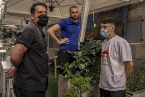 """From left: Alessandro, Emanuele and Antonio are seen outside the pizzeria where they work in the """"Quartieri Spagnoli"""" in Naples, Italy on June 16, 2020. Popular neighborhoods are those that more than others are suffering from the economic crisis generated by the coronavirus. The rate of poverty and unemployment that was higher than the national average in Southern Italy even before the pandemic, increased following the lockdown imposed by the government to counter the spread of the coronavirus, which blocked the country's economy for more than two months."""