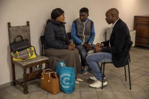 Princess Inyang Okokon (left) speaks with men after celebrating the Sunday mass inside a Pentecostal church in Asti, Northern Italy on January 12, 2020. Princess illegally entered Italy in 1998 as a victim of human trafficking. When she met her future husband Alberto Mossino she was able to pay off her debt of 45000 euros with the madame and interrupt that kind of life. In 2000, together with Alberto, she decided to found the non-profit organization Piam (migrant reception integration project) to help foreign girls victims of human trafficking.
