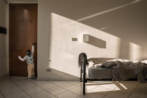 A little boy tries to open a door inside a structure managed by Piam onlus that hosts foreign girls victim of human trafficking in Asti, Northern Italy on January 12, 2020.