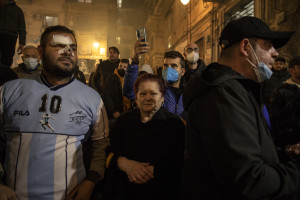 A newsagent and his cat are seen near a poster of the Argentine soccer legend Diego Armando Maradona in Naples, Italy on November 28, 2020.