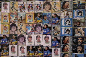 A man is seen near pictures of the Argentine soccer legend Diego Armando Maradona in the Spanish Quarter after the announcement of his death in Naples, Italy, on November 26, 2020.