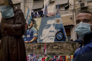 A man holding a funeral poster is seen in the Spanish Quarter after the announcement of the Argentine soccer legend Diego Armando Maradona death in Naples, Italy on November 26, 2020.