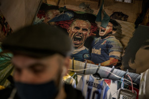 A man is seen near pictures of the Argentine soccer legend Diego Armando Maradona in the Spanish Quarter after the announcement of his death, in Naples, Italy, on November 25, 2020.