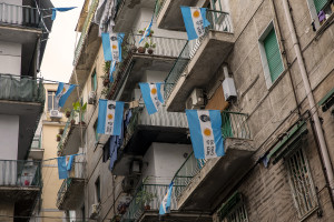 A man is seen near scarves, football shirts and pictures of the Argentine soccer legend Diego Armando Maradona are seen outside San Paolo stadium after the announcement of his death in Naples, Italy on November 27, 2020.