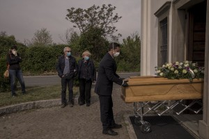 A funeral agency employee carries outiside a church the coffin of a 47 years old man died of coronavirus, while his parents and his wife mourn in the cemetery of Locate Bergamasco, province of Bergamo, Northern Italy on April 16, 2020.