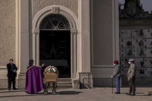 Father Mario Carminati bless the coffin of a coronavirus victim inside the cemetery of Seriate, province of Bergamo, Northern Italy on April 15, 2020.