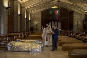 Father Marcello (left) and Father Mario Carminati (right) bless the coffins of coronavirus victims inside San Giuseppe church in Seriate, province of Bergamo, Northern Italy on April 15, 2020.