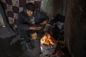 """Ataullah, 25 years old from Afghanistan warms up near a fire inside an abandoned building in Bihac, Bosnia and Herzegovina on January 27, 2021. Ataullah has been in Bosnia for 7 months and has tried the """"game"""" 8 times to continue his journey to Northern Europe and join his family who live in Germany. The Croatian police has always intercepted him and once broke his phone and glasses. Lots of migrants avoid staying inside the Bosnian official refugee camps because of the hard conditions in which they are forced to live and also because the people hosted in the official camps  cannot go out freely."""