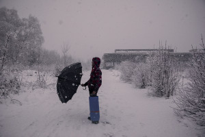 A migrant with an umbrella crosses the snow-covered fields to return to his shelter, found in the rubble of an abandoned factory in Bihac, Bosnia and Herzegovina on January 25, 2021. Lots of migrants avoid staying inside the Bosnian official refugee camps because of the hard conditions in which they are forced to live and also because the people hosted in the official camps  cannot go out freely.