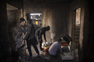 Migrants prepare bread inside an abandoned building in Bihac, Bosnia and Herzegovina on January 27, 2021. Lots of migrants avoid staying inside the Bosnian official refugee camps because of the hard conditions in which they are forced to live and also because the people hosted in the official camps  cannot go out freely.