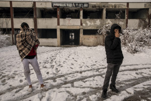 Two migrants are seen outside an abandoned factory in Bihac, Bosnia and Herzegovina on January 26, 2021. Lots of migrants avoid staying inside the Bosnian official refugee camps because of the hard conditions in which they are forced to live and also because the people hosted in the official camps  cannot go out freely.
