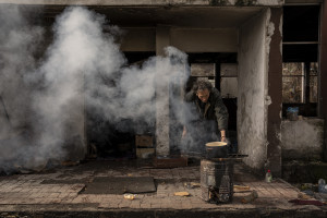 A migrant cooks outisde an abandoned factory in Bihac, Bosnia and Herzegovina on January 23, 2021. Lots of migrants avoid staying inside the Bosnian official refugee camps because of the hard conditions in which they are forced to live and also because the people hosted in the official camps  cannot go out freely.