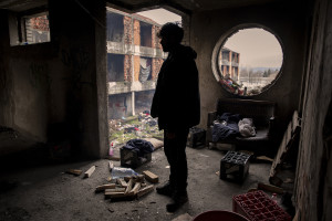 """Ataullah, 25 years old from Afghanistan is seen inside an abandoned building in Bihac, Bosnia and Herzegovina on January 24, 2021. Ataullah has been in Bosnia for 7 months and has tried the """"game"""" 8 times to continue his journey to Northern Europe and join his family who live in Germany. The Croatian police has always intercepted him and once broke his phone and glasses."""