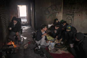 A migrant (left) warms up near a fire while another group of migrants (right) have a breakfast inside an abandoned building in Bihac, Bosnia and Herzegovina on January 27, 2021. Lots of migrants avoid staying inside the Bosnian official refugee camps because of the hard conditions in which they are forced to live and also because the people hosted in the official camps  cannot go out freely.