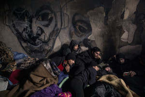 Migrants from Afghanistan and Pakistan watch a football match on a smartphone inside an abandoned building in Bihac, Bosnia and Herzegovina on January 21, 2021. Lots of migrants avoid staying inside the Bosnian official refugee camps because of the hard conditions in which they are forced to live and also because the people hosted in the official camps  cannot go out freely.