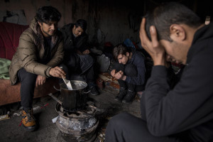 Migrants cook inside an abandoned building in Bihac, Bosnia and Herzegovina on January 21, 2021. Lots of migrants avoid staying inside the Bosnian official refugee camps because of the hard conditions in which they are forced to live and also because the people hosted in the official camps  cannot go out freely.